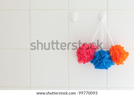 Three nylon body scrubbers or puffs hanging from a hook in a white tile shower.