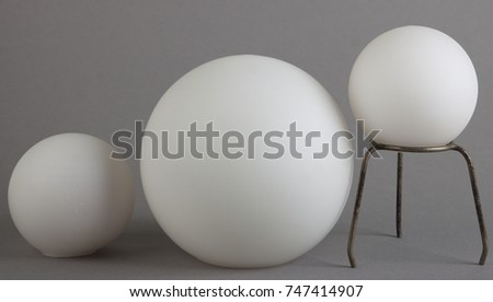Three objects (white orbs) different heights: small object, big object, small object placed on a stand.