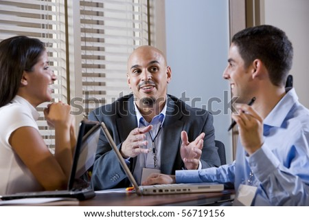 Three office colleagues having discussion at desk