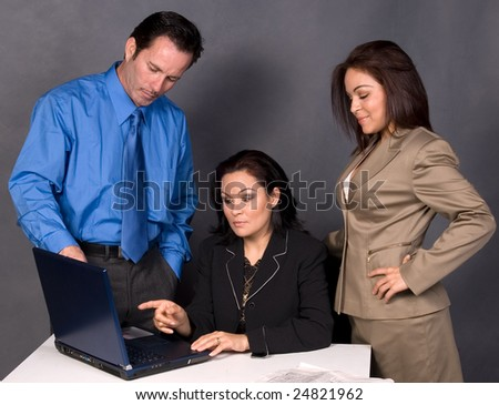 Three office workers, one man and two women standing around a desk in front of a computer having a discussion