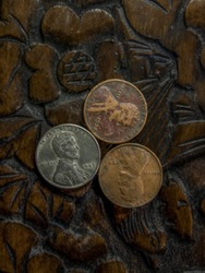 Three old American pennies side by side from the years 1943, 1940, 1936 sitting on top of wood carved flowers.