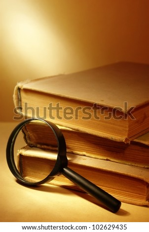 three old books and magnifying glass