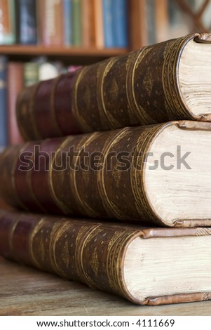 Three old books in front of library shelves #4111669