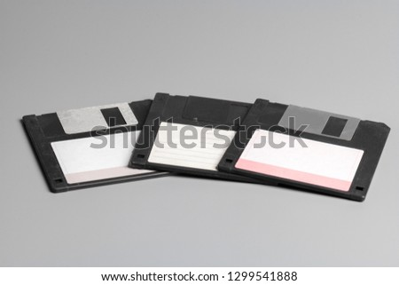 Three old computer diskette over grey  background