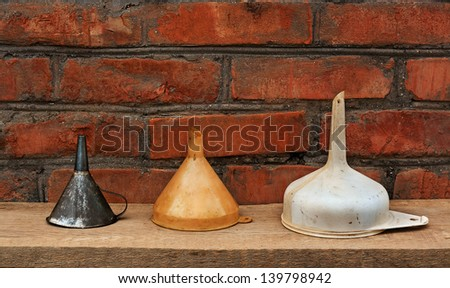 three old fashioned funnels from metal and plastic on rustic wooden surface