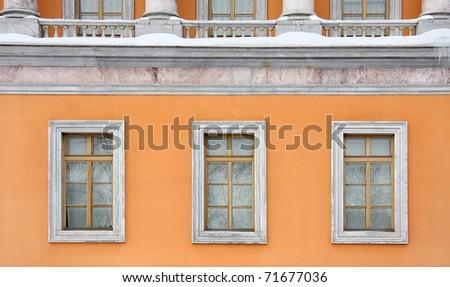 Three old windows on the orange wall