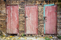 Three old wooden plank doors in a wall