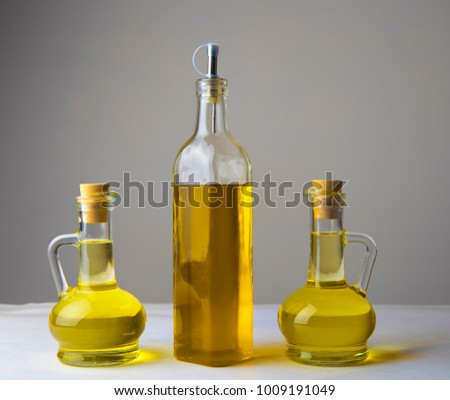 three olive oil glass transparent bottle with cork stand on white table on kitchen space room, on dark black background Empty space for inscription