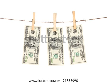 Three one hundred dollar bills is hanging on a rope with wooden clothespin isolated on white