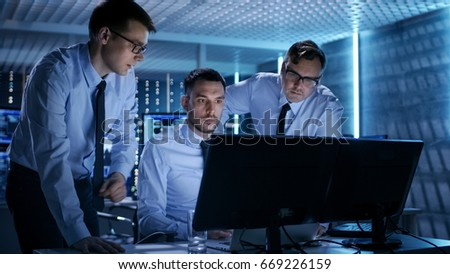 Three Operations Engineers Solving Problem in a Monitoring Room. In System Control Room Multitple Displays Show Various Data.