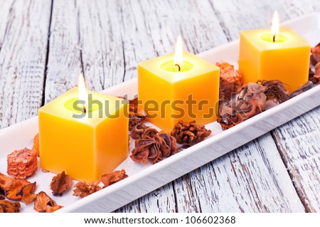 three orange candles with flowers on a white wooden board