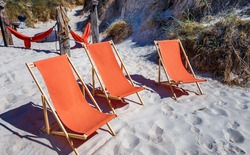 Three orange color deck chairs waiting for tourists at a sand dune in Northern jutland,  Denmark