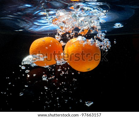three oranges in water with bubbles. On a black background