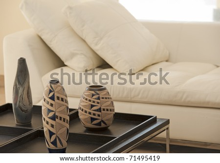 Three ornate vases on a wooden table in living room next to white sofa