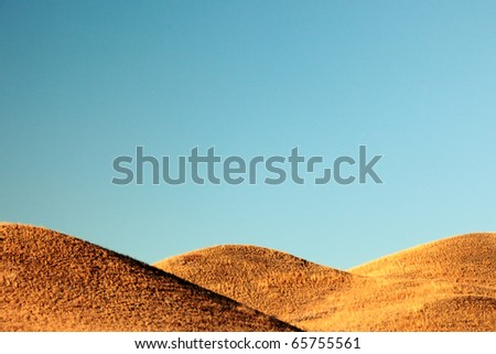 Three overlapping hills against a clear steel blue sky.
