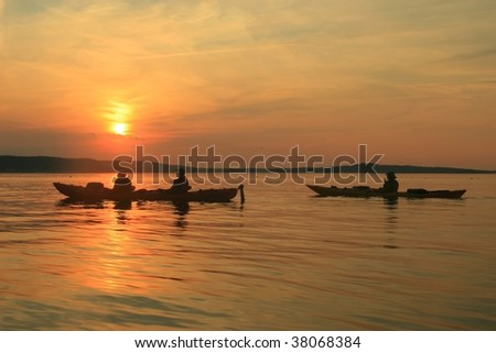 Three paddlers in kayaks at sunset in Frenchman Bay near Bar Harbor, ME