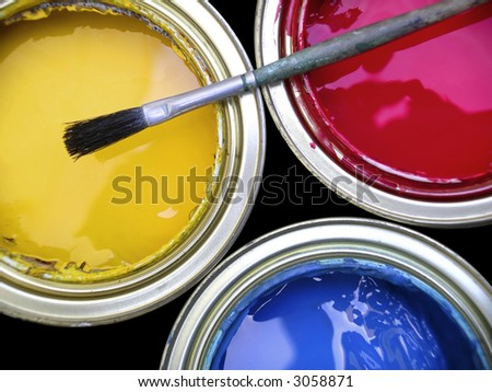 Three paint cans with one brush on top - stock photo