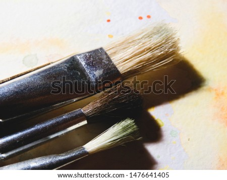 Three paintbrushes on watercolor paper. #1476641405