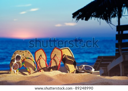 Three pair of beach sandals and glasses on the beach