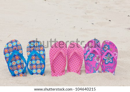 Three pairs bath slippers in a row stuck in the sand beach - stock photo
