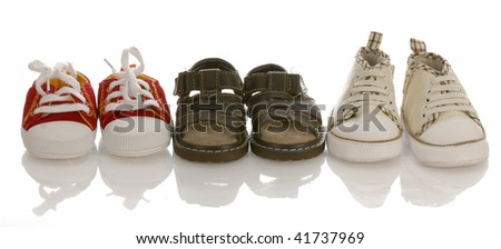 three pairs of baby or infant shoes with reflection on white background