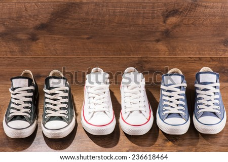 three pairs of cool youth white gym shoes with red  stripes  on brown wooden floor  standing in line with copy place  top view