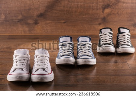 three pairs of cool youth white gym shoes with red  stripes  on brown wooden floor  standing in line with perspective