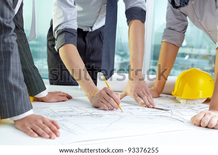 Three pairs of hands sketching a housing project