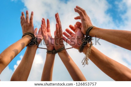 Three pairs of human hands tied up together with rope