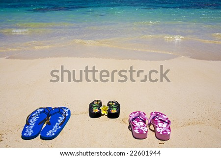 three pairs of sandals sit on the sand at water's edge by a lagoon in Hawaii