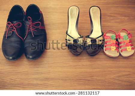 Three pairs of shoes: men, women and children. Baby sandals stand next to women\'s shoes. concept of the child is friends with his mother. Idea parents divorced, child remained with mother. Toned image