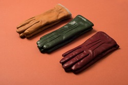 Three pairs of stylish leather gloves. Expensive gloves lie on a brown background. Showcase with leather gloves. Choice of gloves. fashionable accessories