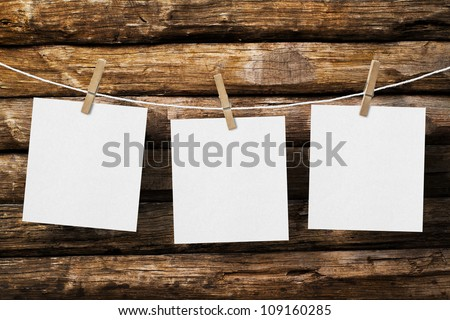 three  paper attach to rope with clothes pins on old wooden background