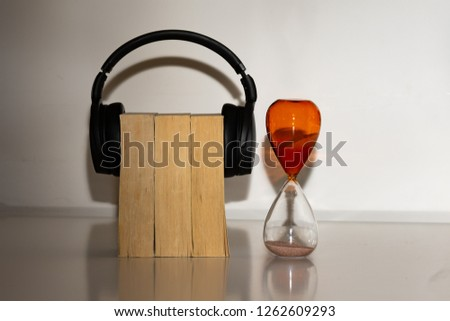 Three paper back books with wireless headphones over them, representing an audio book, next to an orange hourglass sand timer to represent the time taken or saved to listen to audiobooks #1262609293