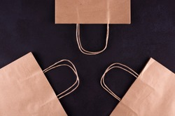 Three paper bags with handles on a black table. View from above.