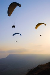 Three paraglider in the evening sky