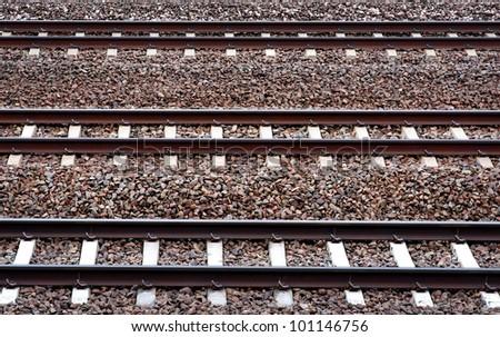 Three parallel railway tracks on pebbles