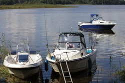 Three parked motor boats near river bank on green far shore background, Volga river calm water at quiet summer day, Russian river landscape, boating recreation