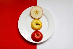 Three parts of an Apple on a plate top view