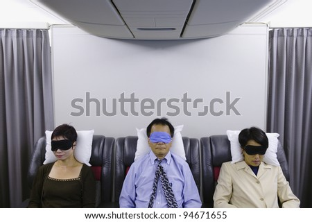 Three passengers sleeping on airplane