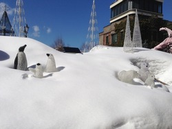 Three penguin and polar bear statue on snow and blue sky background