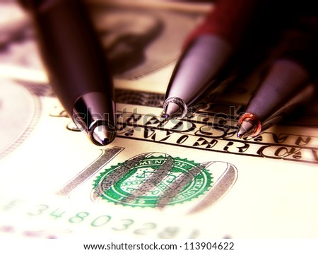 Three pens on a dollar banknote.