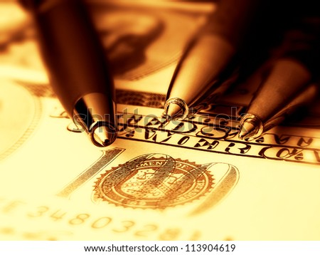 Three pens on a dollar banknote. Gold tone.