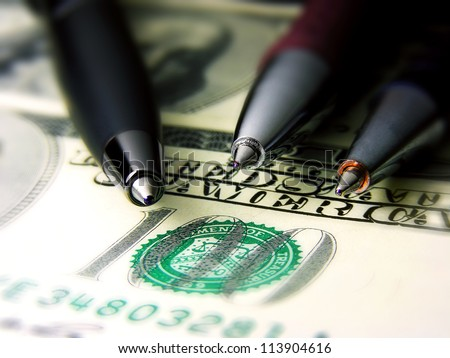 Three pens on a dollar banknote. Small depth of field
