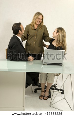 Three people are in a business meeting.  They are smiling and looking at each other.  There is a laptop on the table.  Vertically framed shot.