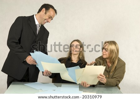 Three people are in a business meeting.  They are smiling and looking at some pieces of paper .  The women are sitting and the man is standing.  Horizontally framed shot.