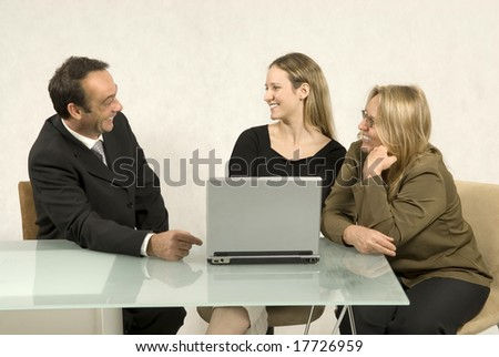 Three people are sitting together in a room at a table. They are all looking at each other.