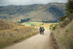 Three people cycling the Otago Central Rail Trail among mountain ranges between Waipiata and Middlemarch, South Island, New Zealand