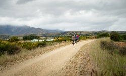 Three people cycling the Otago Central Rail Trail in the countryside, South Island, New Zealand