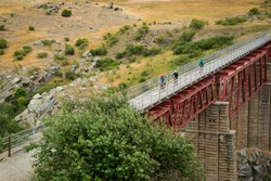 Three people cycling the Otago Central Rail Trail on the Poolburn Viaduct, South Island, New Zealand